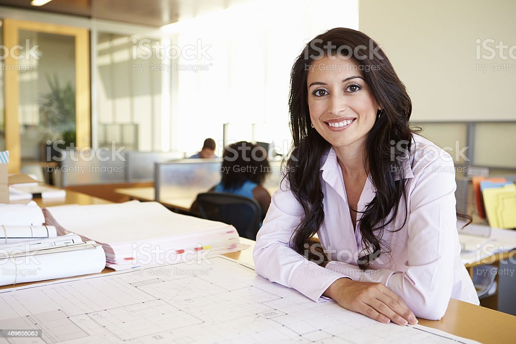 Female Architect Studying Plans In Office stock photo