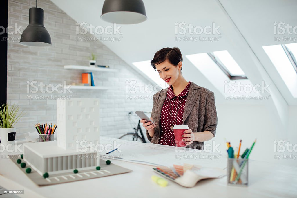 Female Architect Texting On Smart Phone In Her Office. stock photo