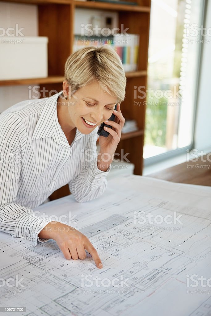 Female architect using cellphone with a blueprint on desk royalty-free stock photo