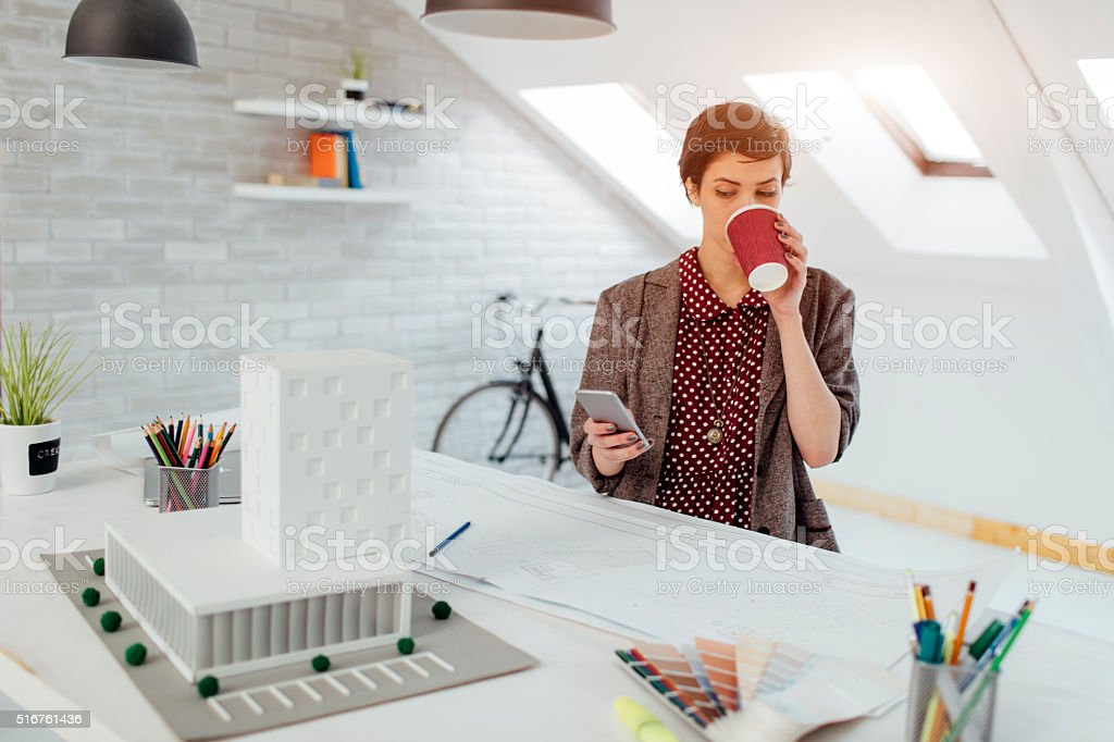 Female Architect Using Smart Phone In Her Office. stock photo