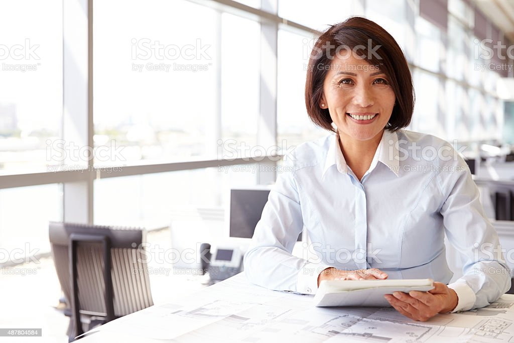 Female architect using tablet computer, looking to camera stock photo