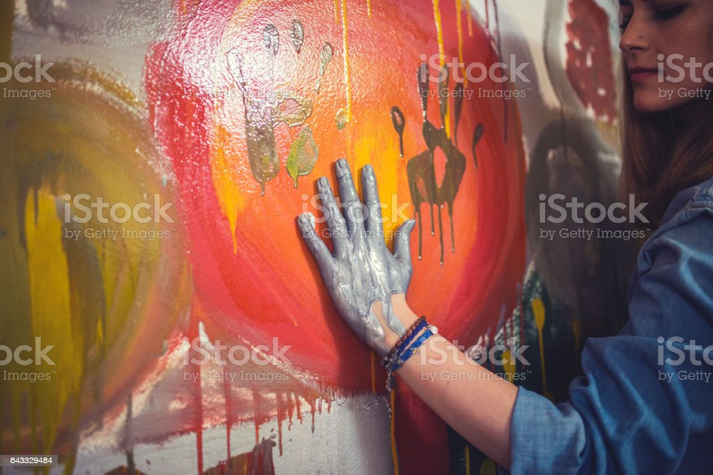 Female artist hand printing with paint stock photo