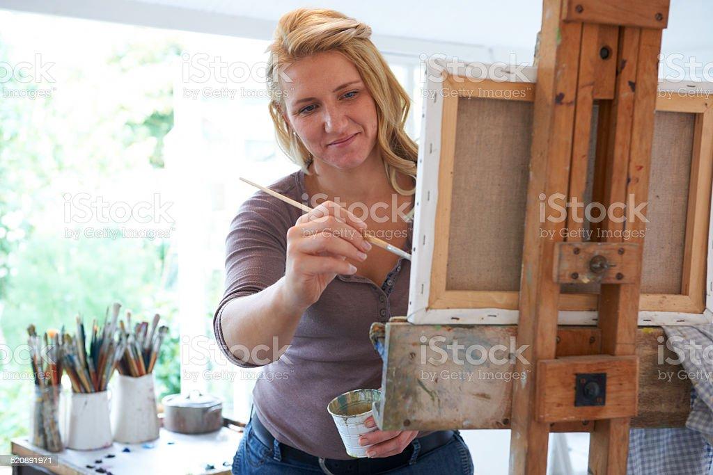 Female Artist Painting In Studio stock photo