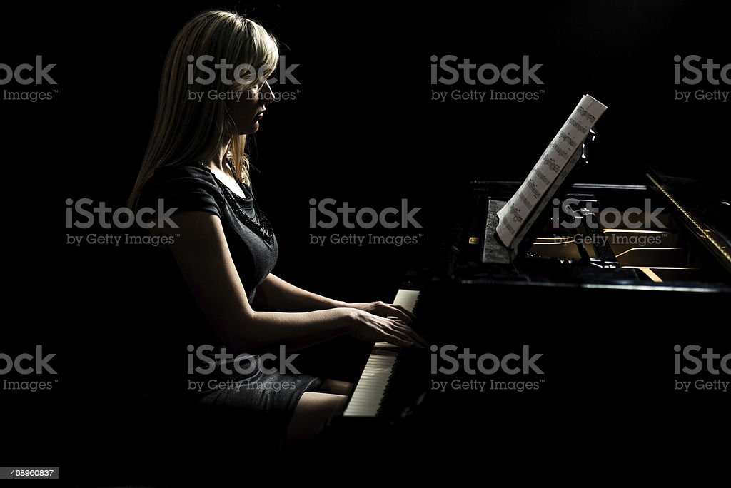 Female artist playing the piano. stock photo