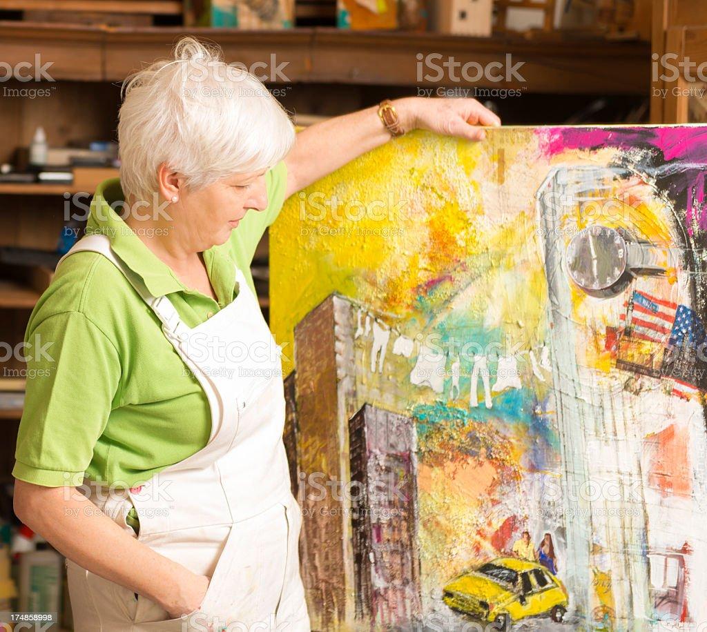 Female artist standing shows painting art studio royalty-free stock photo