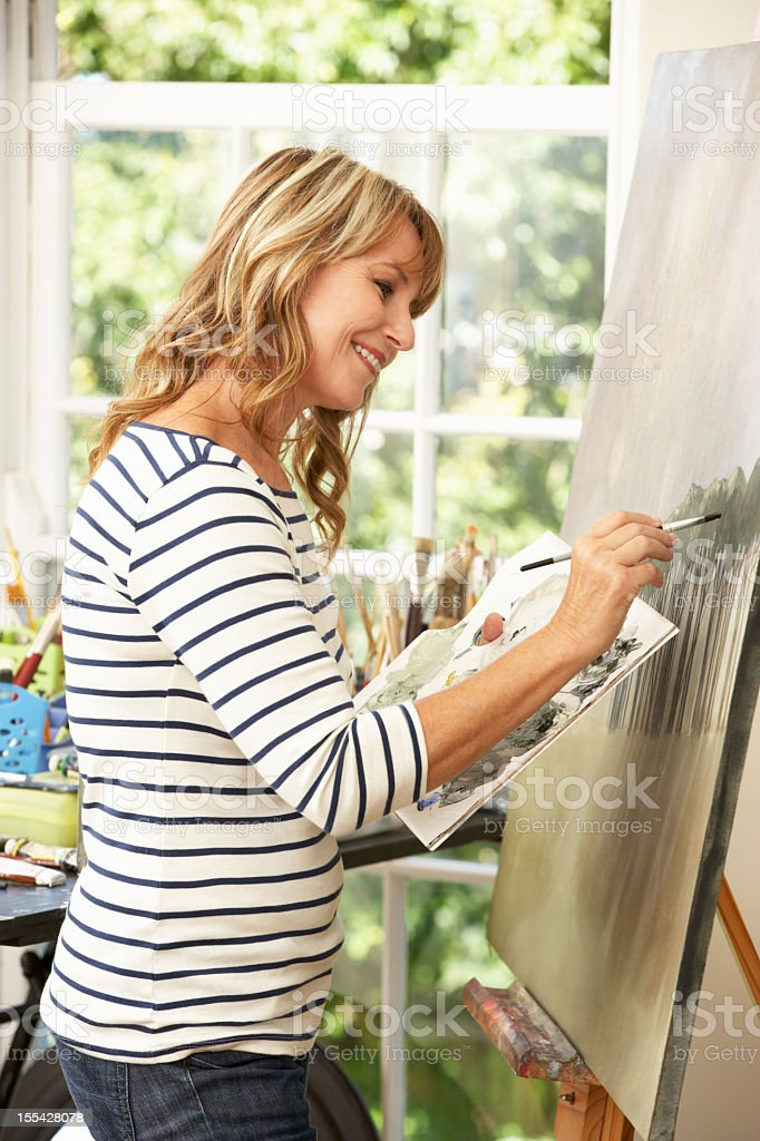 Female artist working on a painting in the studio royalty-free stock photo