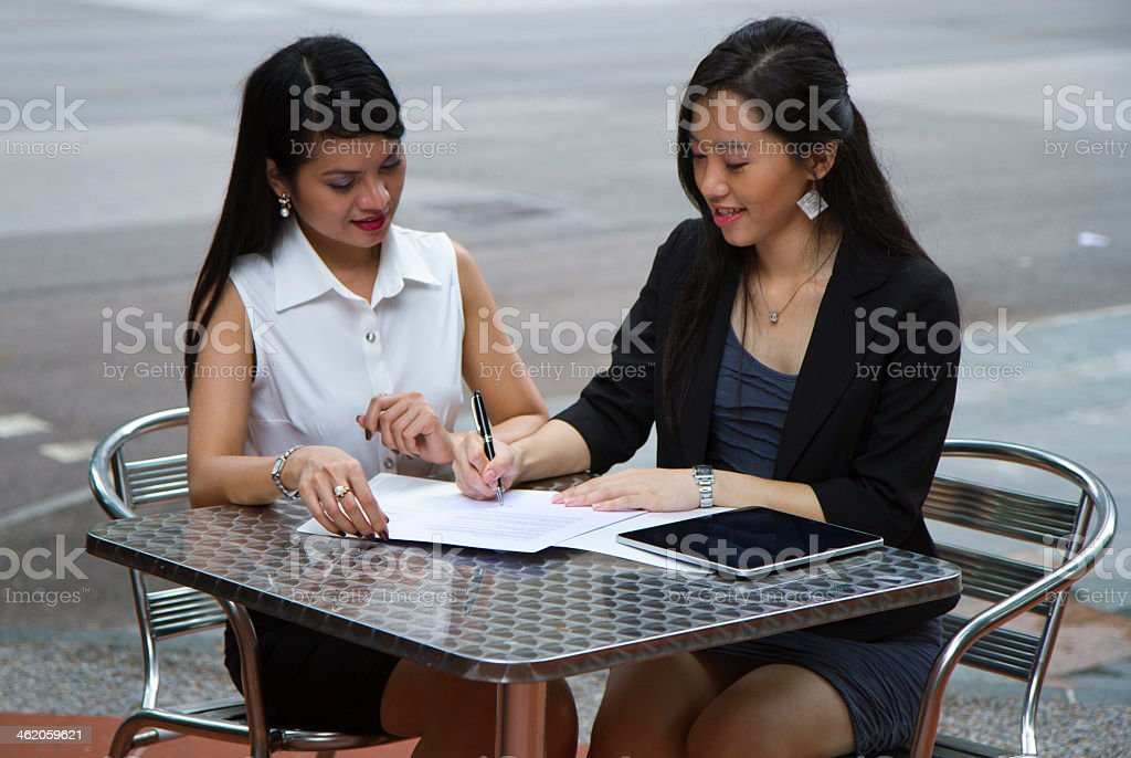 Female asian business executives discussing a contract stock photo