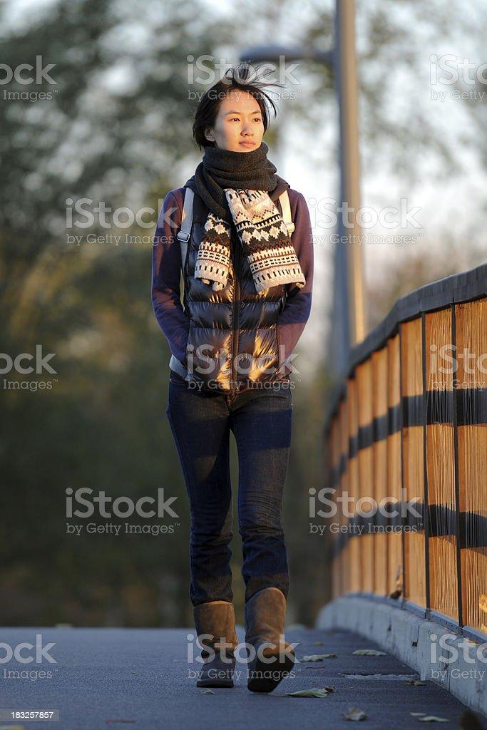 Female Asian Student Walkig On Bridge At Sunset - XLarge royalty-free stock photo