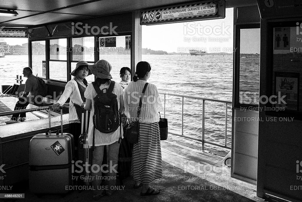 Female asian tourists waiting in a vaporetto stop, Venice royalty-free stock photo