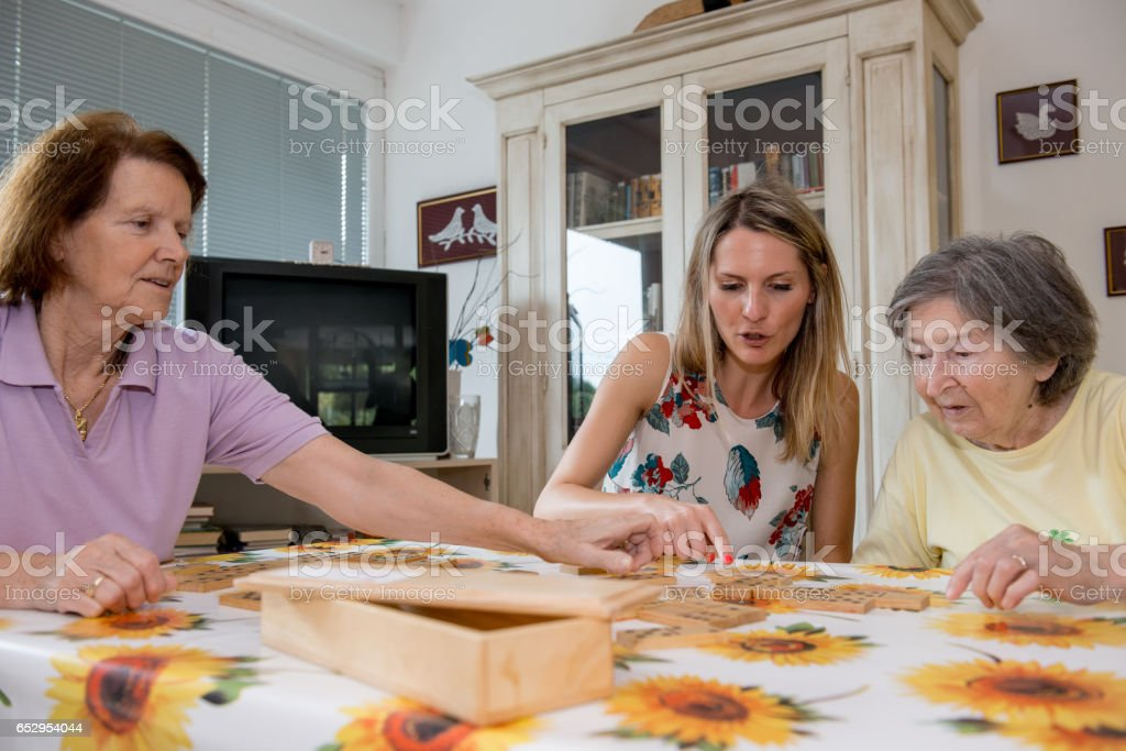 Female Assistant Play Domino With Seniors At The Nursery Home stock photo