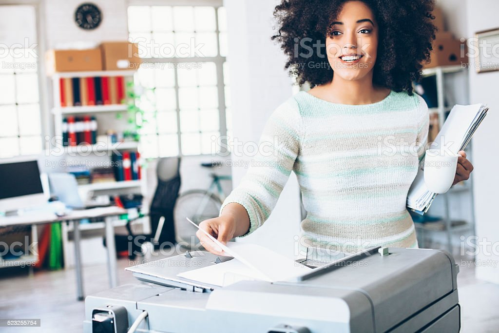 Female assistant using copy machine at workplace stock photo