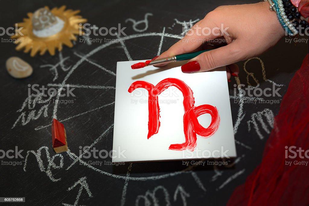 Female astrologer draws capricorn zodiac  sign on white tile stock photo