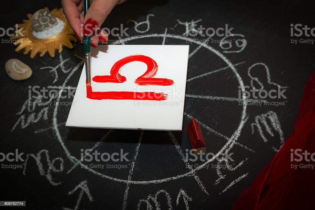 Female astrologer draws libra zodiac sign on white tile stock photo