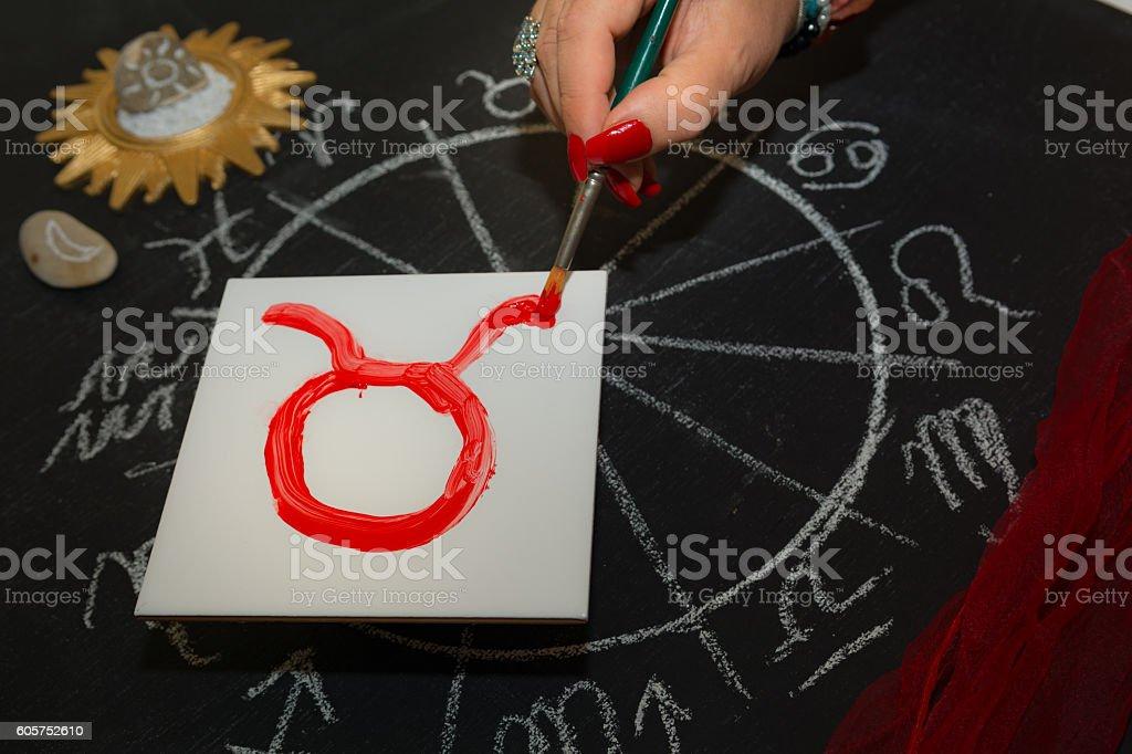 Female astrologer draws taurus zodiac sign on white tile stock photo