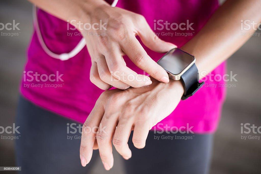 Female athlete adjusting pulse trace stock photo