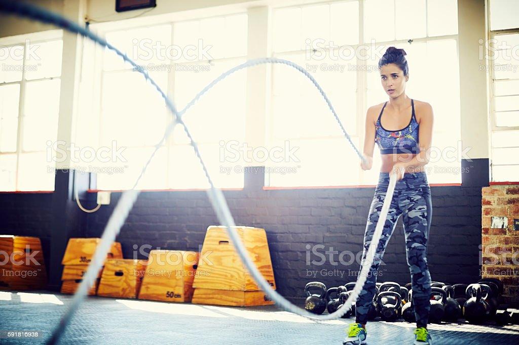 Female athlete doing battling rope exercise at gym stock photo