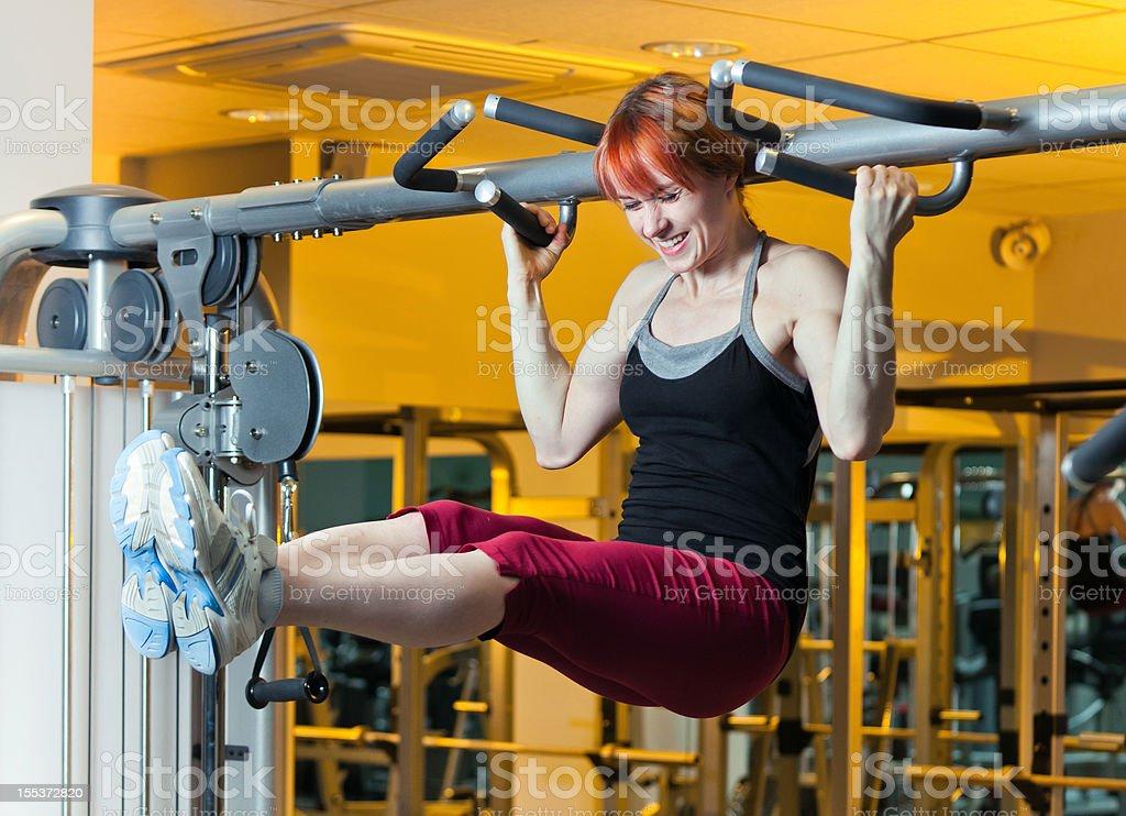 Female athlete doing exercise on horizontal bar stock photo