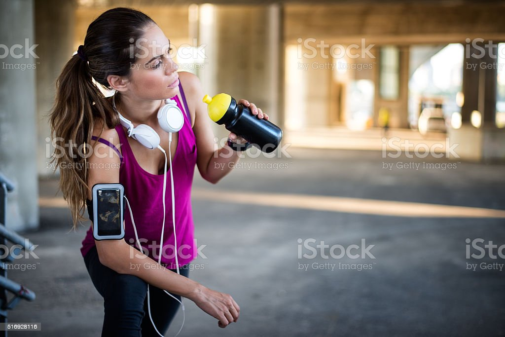 Female athlete drinking from sports bottle stock photo