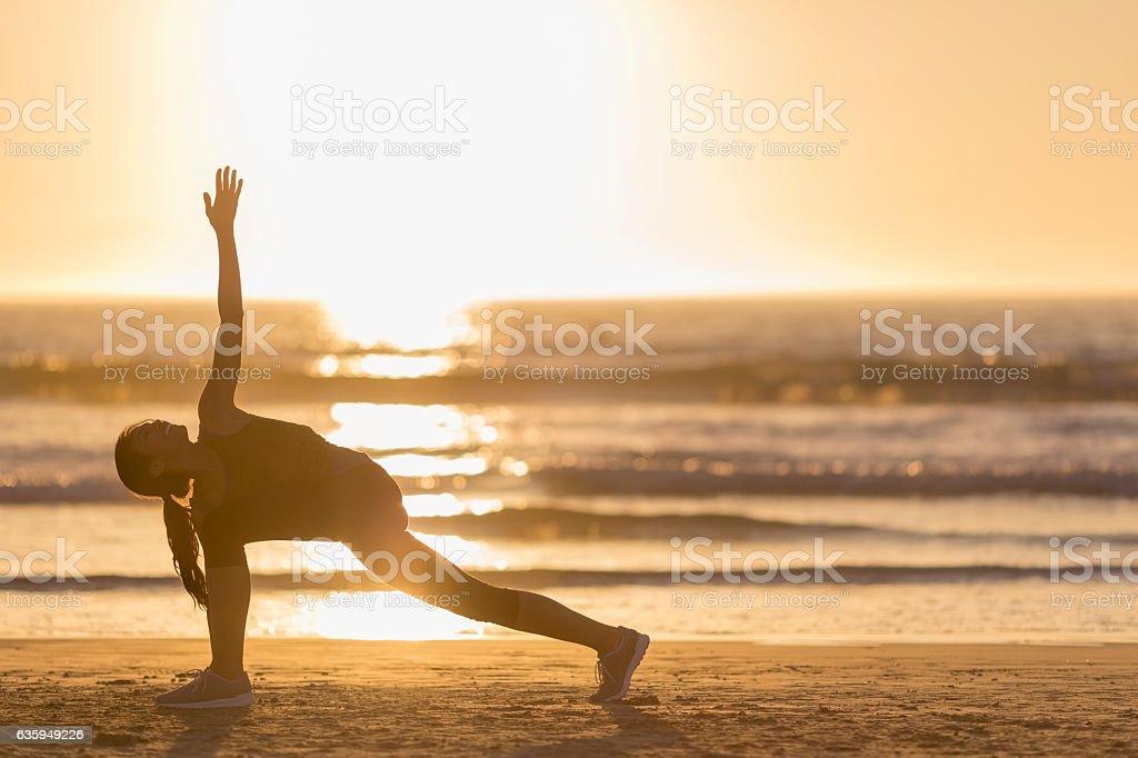 Female athlete exercising at beach during sunset stock photo