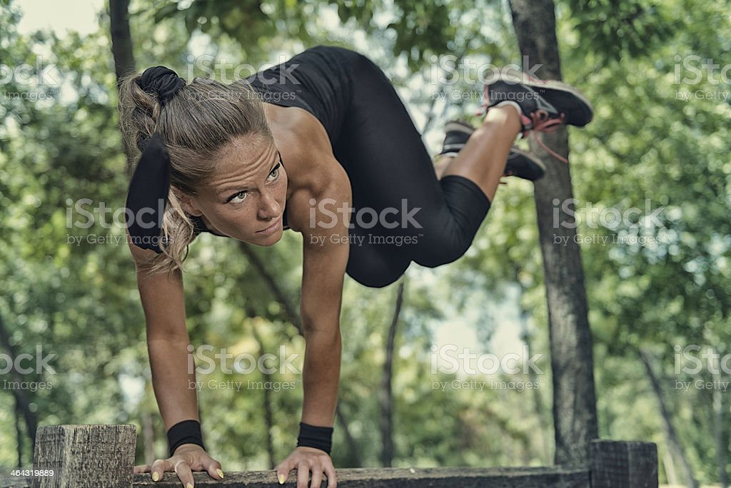Female athlete exercising on fitness trail stock photo