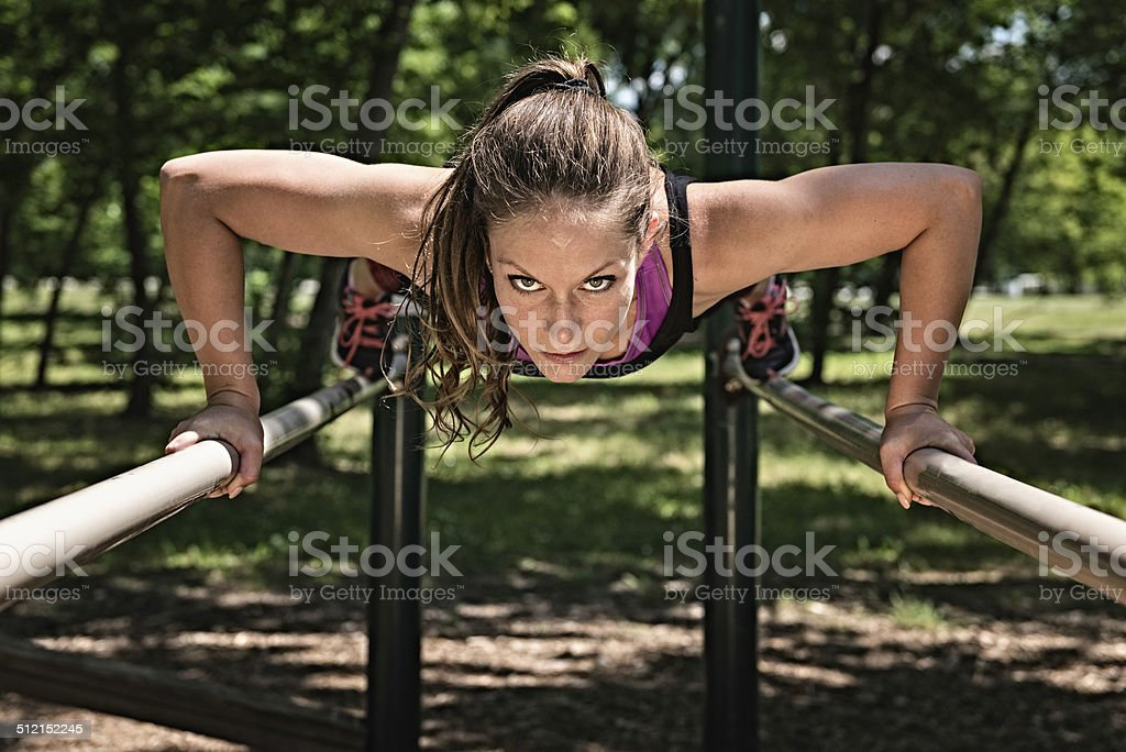 Female athlete exercising on parallel bars stock photo