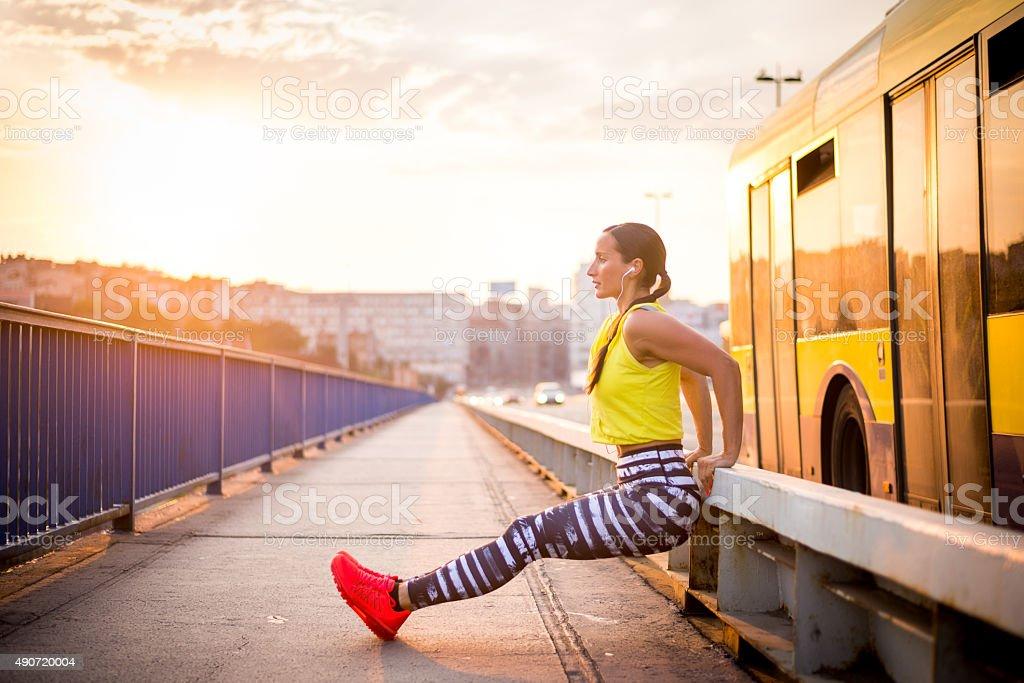 Female athlete exercising on the bridge stock photo
