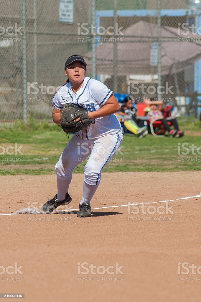Female athlete fielding a ball at 3rd stock photo