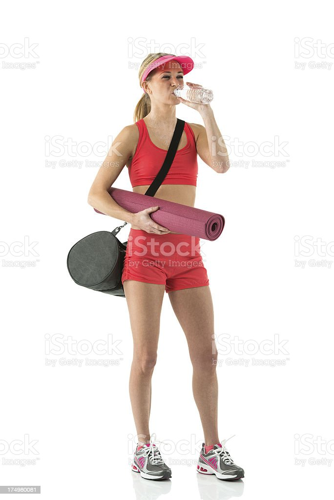 Female athlete holding a yoga mat and drinking water royalty-free stock photo