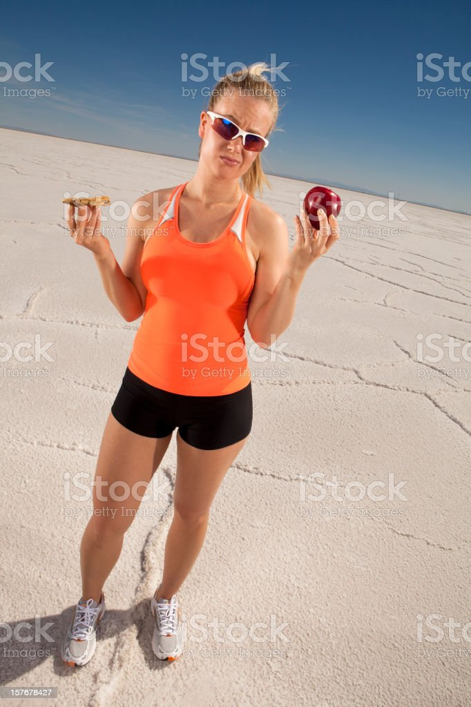 Female Athlete Holding an Apple and Cookie royalty-free stock photo