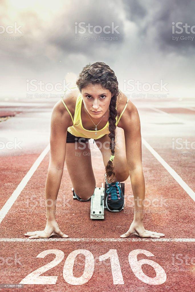 Female athlete in the starting blocks stock photo