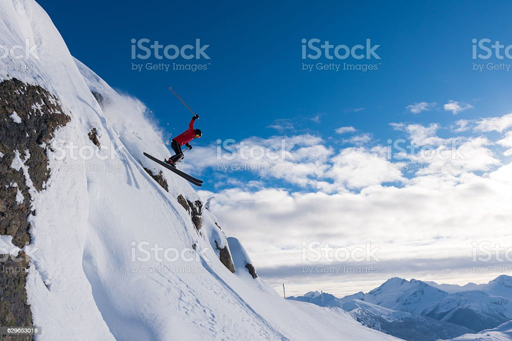 Female athlete jumping off a cliff stock photo