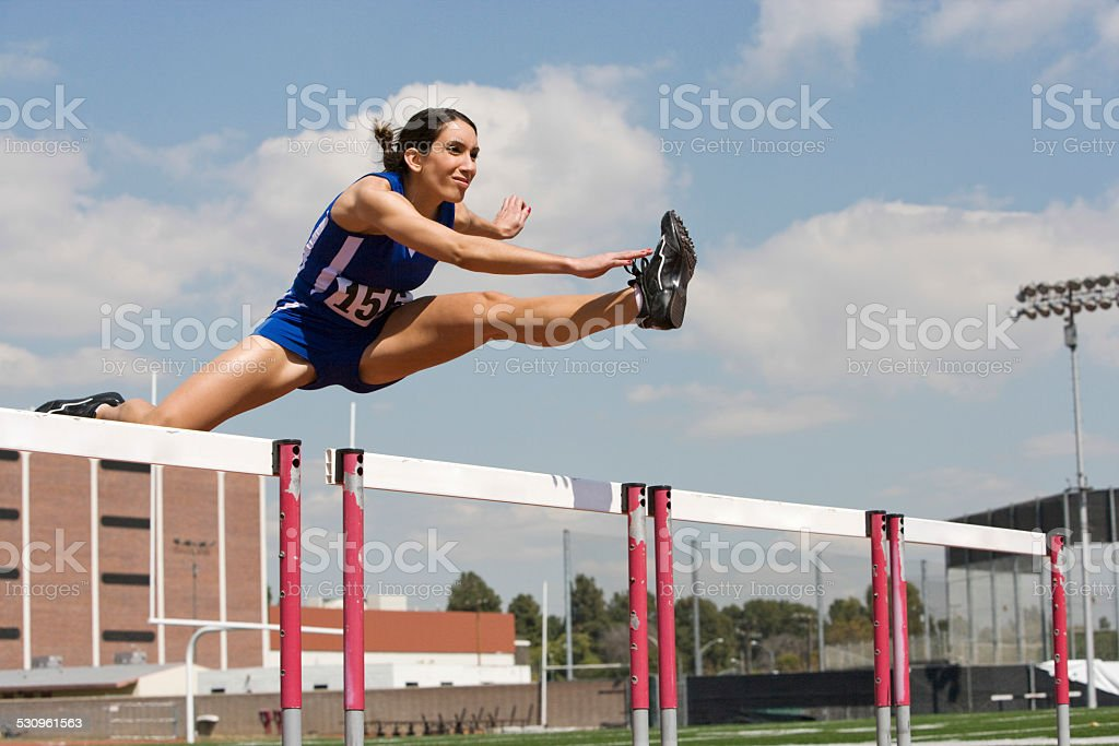 Female Athlete Jumping Over A Hurdles stock photo