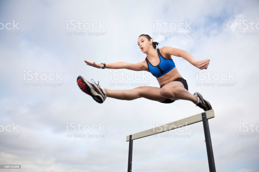 Female Athlete Jumping Over Hurdle During Track Meet stock photo