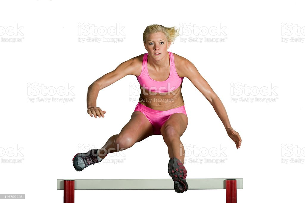 Female Athlete Jumping Over Hurdle royalty-free stock photo
