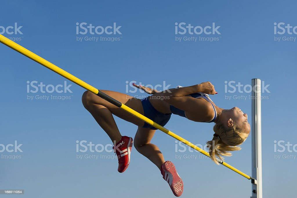 Female athlete jumping over the lath stock photo