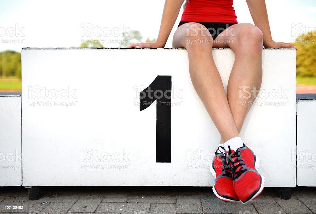female athlete on winners podium stock photo