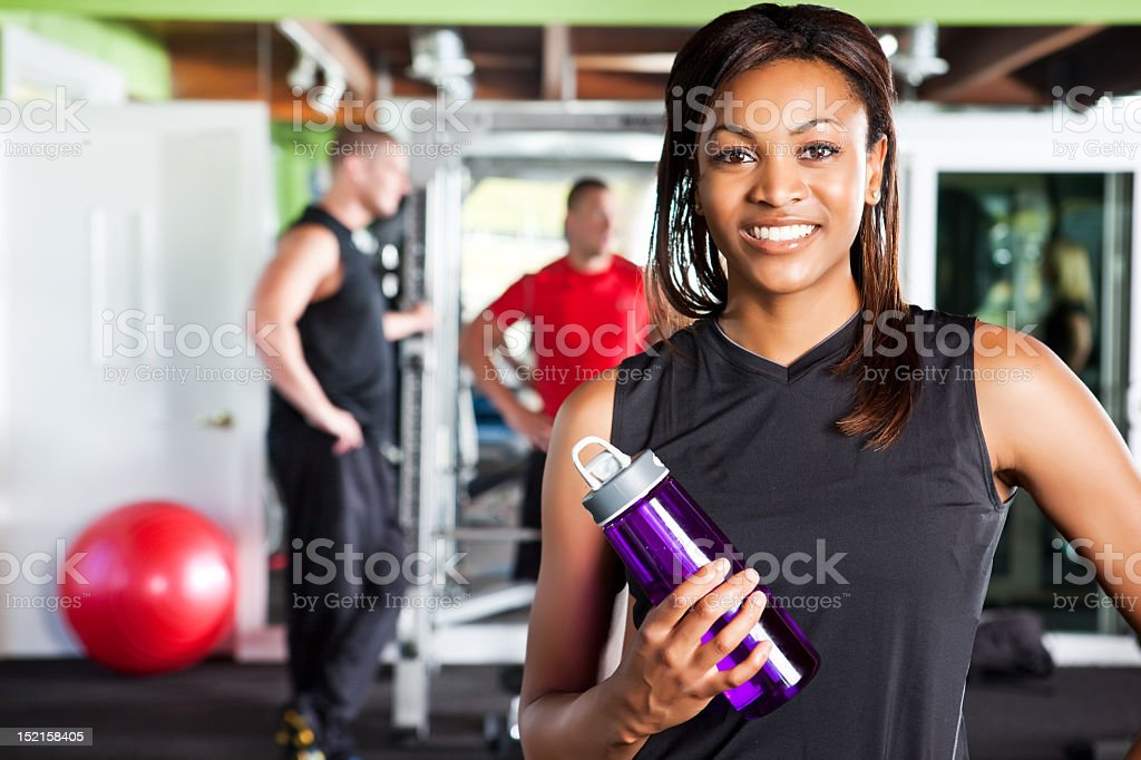 Female athlete posing with a metal water bottle at the gym stock photo