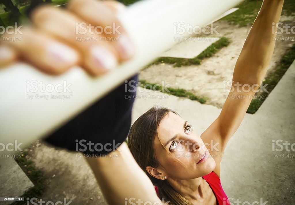 Female athlete prepares for action pull-ups outdoors stock photo