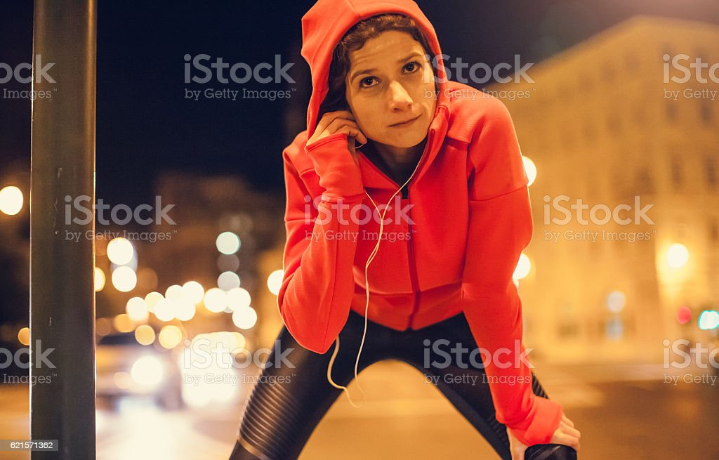 Female Athlete Preparing Herself for a Late Night Jogging stock photo