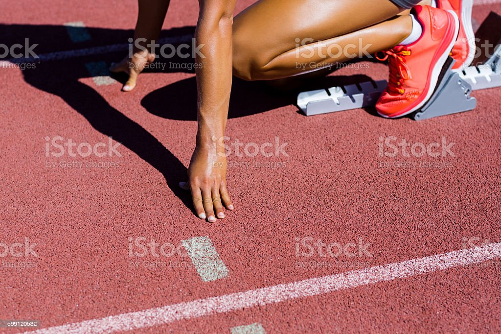 Female athlete ready to run on running track stock photo