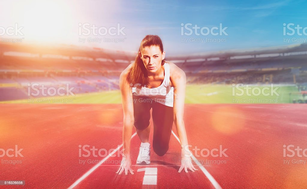 Female athlete ready to run on sports track stock photo