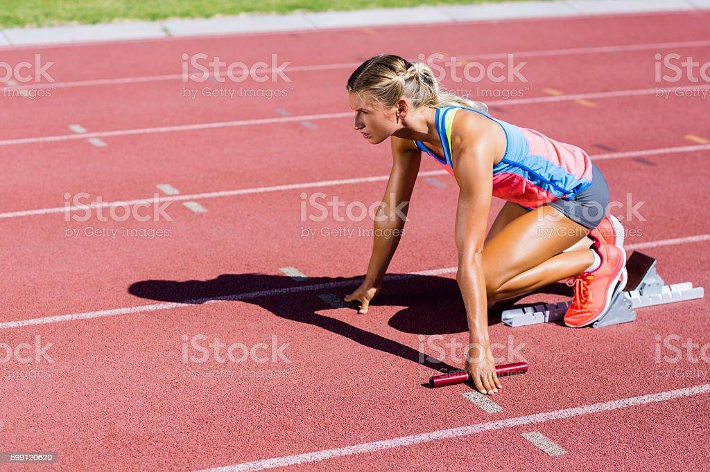 Female athlete ready to start the relay race stock photo