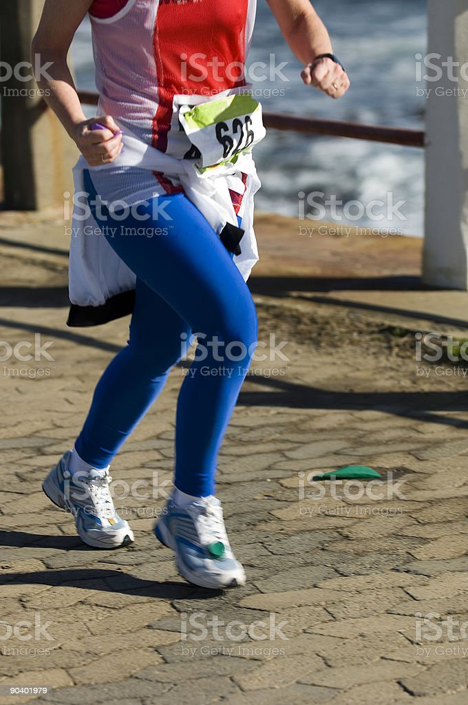 Female athlete running on a paved road stock photo