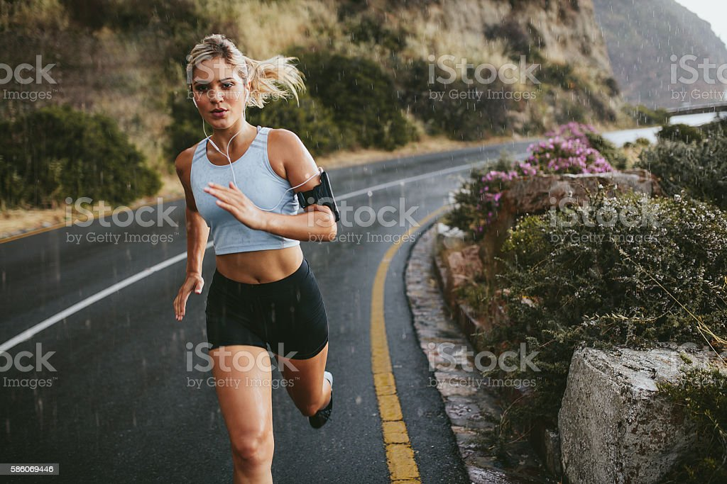 Female athlete running outdoors on highway stock photo