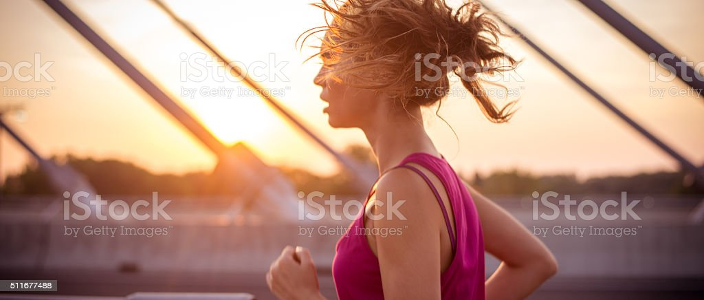 Female athlete running over the bridge in the morning stock photo