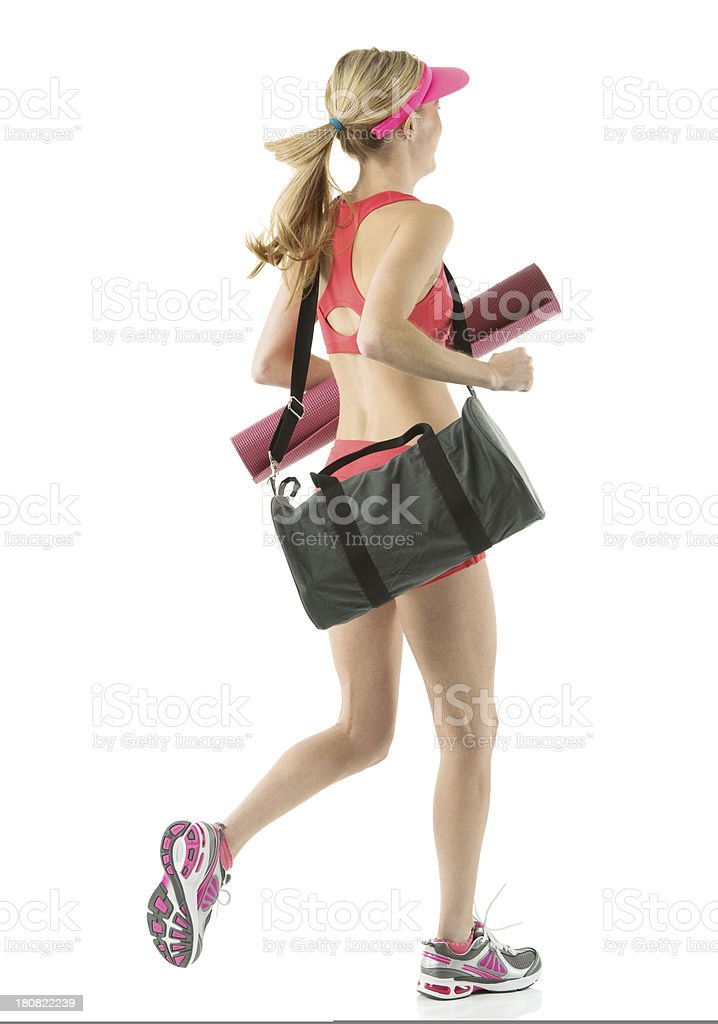 Female athlete running with exercise mat and gym bag royalty-free stock photo