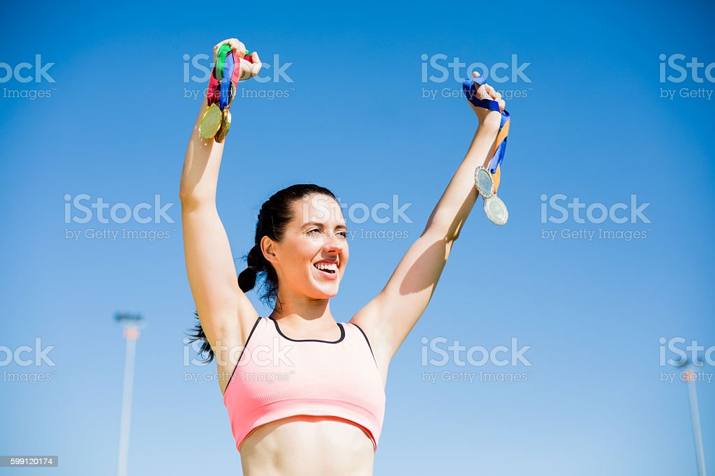 Female athlete showing her gold medals stock photo