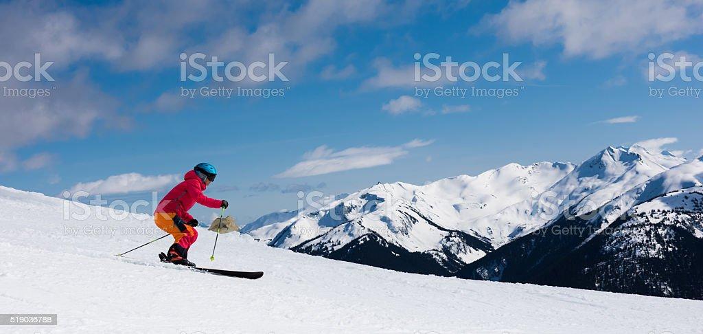 Female athlete skiing in the mountains stock photo