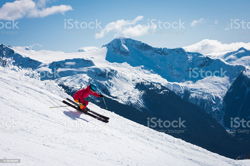 Female athlete skiing in the mountains stock photo