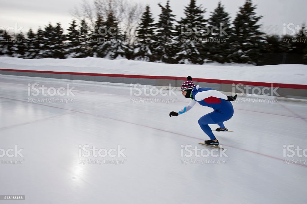 Female Athlete Speed Skating on a Cold Winter Day. stock photo
